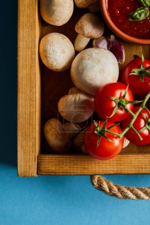 Photo pour Top view of tomato sauce in bowl near mushrooms, red cherry tomatoes and garlic cloves in wooden box on blue - image libre de droit