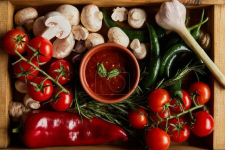Photo for Top view of tomato sauce with basil leaves near cherry tomatoes, green chili peppers, mushrooms and rosemary in wooden box - Royalty Free Image