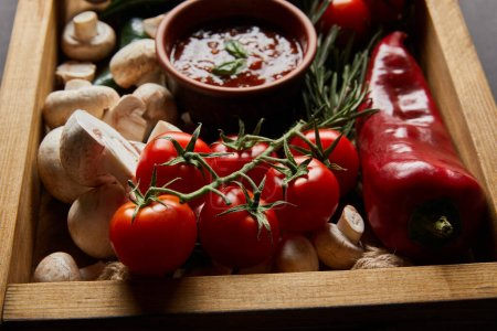 Photo for Selective focus of cherry tomatoes, mushrooms, tomato sauce near rosemary and red chili pepper in wooden box - Royalty Free Image