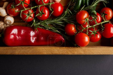Photo for Top view of cherry tomatoes, mushrooms near rosemary and red chili pepper in wooden box on black - Royalty Free Image