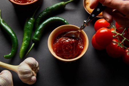 Photo for Cropped view of one person holding spoon near tasty tomato sauce and vegetables on black - Royalty Free Image