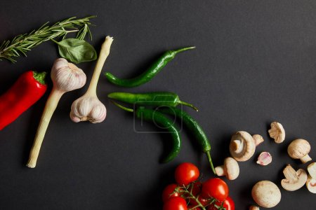 Photo for Top view of ripe cherry tomatoes, garlic, rosemary, basil leaves, green chili peppers and mushrooms on black - Royalty Free Image