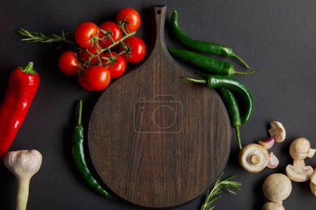 Photo for Top view of wooden cutting board near ripe cherry tomatoes, garlic, rosemary, green chili peppers and mushrooms on black - Royalty Free Image