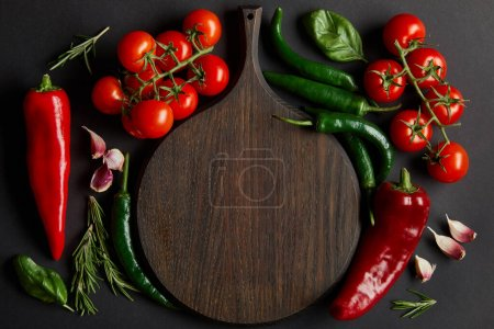 Photo for Top view of wooden chopping board near ripe cherry tomatoes, garlic cloves, rosemary, basil leaves and green chili peppers on black - Royalty Free Image