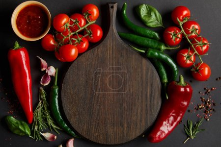 Photo for Top view of chopping board near ripe cherry tomatoes, garlic cloves, rosemary, peppercorns, basil leaves and green chili peppers on black - Royalty Free Image