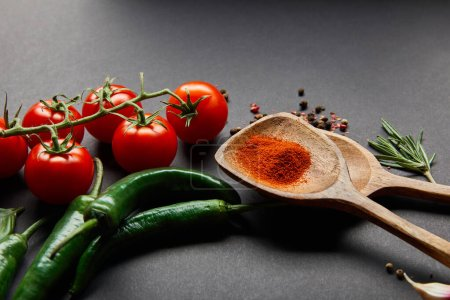 Photo for Red cherry tomatoes, rosemary, peppercorns, wooden spoons with paprika powder and green chili peppers on black - Royalty Free Image