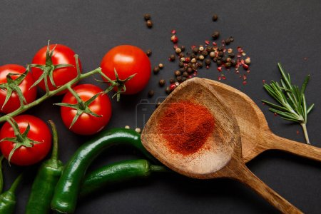 Photo for Top view of red cherry tomatoes, rosemary, peppercorns, wooden spoons with paprika powder and green chili peppers on black - Royalty Free Image