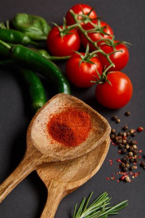 Photo for Top view of ripe cherry tomatoes, rosemary, peppercorns, wooden spoons with paprika powder and green chili peppers on black - Royalty Free Image