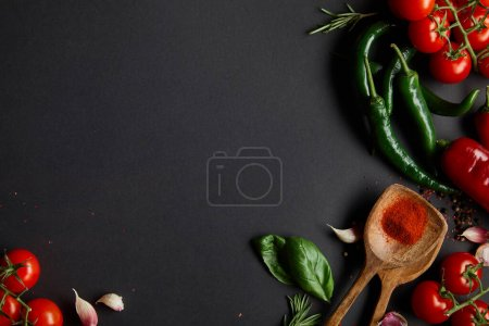 Photo for Top view of organic cherry tomatoes, garlic cloves, fresh rosemary, peppercorns, basil leaves and green chili peppers on black - Royalty Free Image