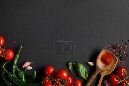 Photo for Top view of ripe cherry tomatoes, garlic cloves, fresh rosemary, peppercorns, basil leaves and green chili peppers on black - Royalty Free Image