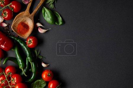 vrchní pohled na cherry rajčata, stroužky česneku, čerstvá rozmarýna, pepřová zrna, listy bazalky a zelené chilli papričky na černém