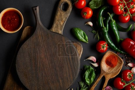 Photo for Top view of cherry tomatoes, garlic cloves, tomato sauce, rosemary, peppercorns, and green chili peppers near chopping boards on black - Royalty Free Image