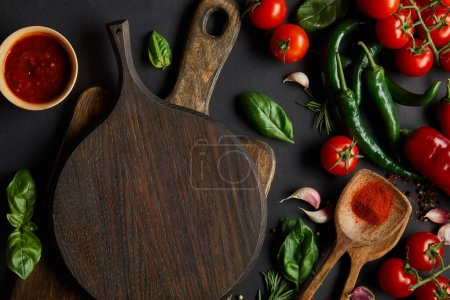 Photo for Top view of red cherry tomatoes, tomato sauce, peppercorns, herbs and green chili peppers near chopping boards on black - Royalty Free Image