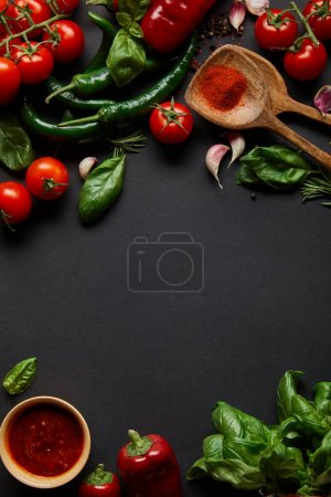 Photo for Top view of red cherry tomatoes, tomato sauce in bowl, peppercorns, herbs and green chili peppers on black - Royalty Free Image