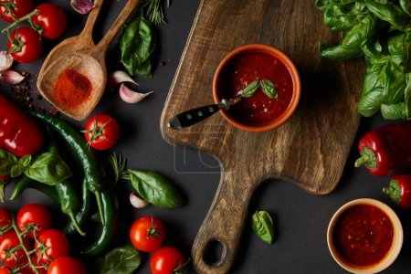 Photo for Top view of red cherry tomatoes, tomato sauce, peppercorns, herbs and green chili peppers near cutting board on black - Royalty Free Image