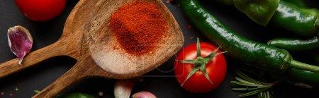 Photo pour Concept horizontal de tomates cerises rouges, herbes et piments près des cuillères avec de la poudre de paprika sur noir - image libre de droit