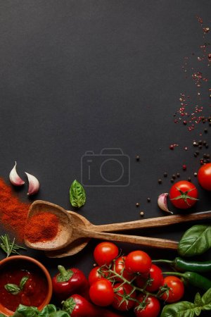 Photo for Top view of red cherry tomatoes, spicy chili peppers, tomato paste, garlic cloves and fresh herbs near spoons with paprika powder on black - Royalty Free Image