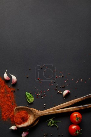Photo for Top view of red cherry tomatoes, garlic cloves and fresh herbs near spoons with paprika powder on black - Royalty Free Image