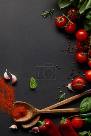 Photo for Top view of cherry tomatoes, spicy chili peppers, garlic cloves and fresh herbs near spoons with paprika powder on black - Royalty Free Image