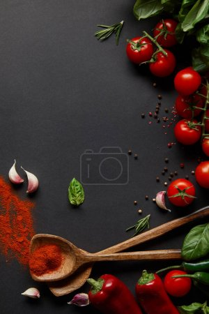 top view of cherry tomatoes, spicy chili peppers, garlic cloves and fresh herbs near spoons with paprika powder on black