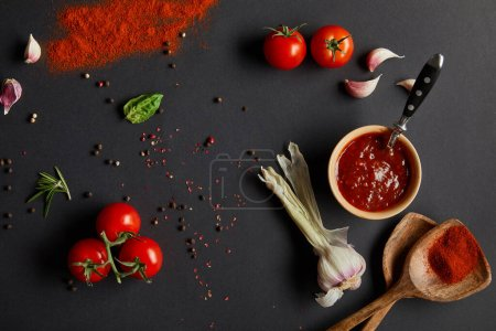 Photo for Top view of red cherry tomatoes, garlic cloves and fresh herbs near wooden spoons with paprika powder on black - Royalty Free Image
