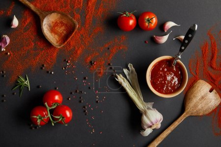 Photo for Top view of ripe cherry tomatoes, garlic cloves and fresh herbs near wooden spoons with paprika powder on black - Royalty Free Image
