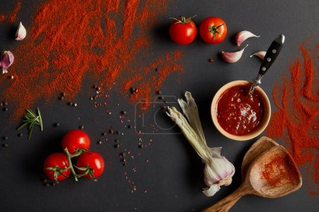 Photo for Top view of cherry tomatoes and fresh herbs near spoons with paprika powder on black - Royalty Free Image