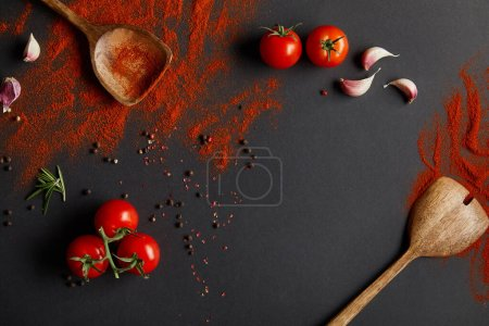 Photo for Top view of tasty cherry tomatoes and fresh herbs near spoons with paprika powder on black - Royalty Free Image