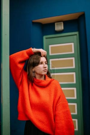 Young woman leaning on a column with red pullover in a colorful house