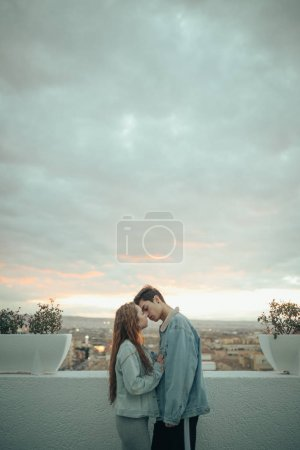 young couple kissing at sunset