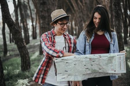 young couple hikers with map in forest