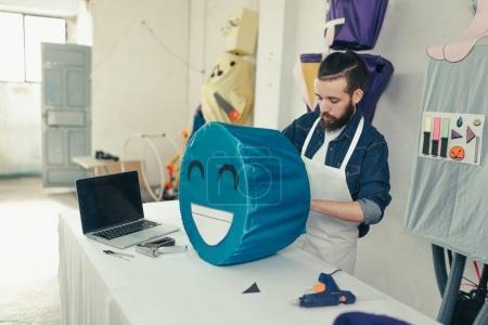 Photo pour Jeune artisan dans l'atelier d'artisanat personnalisant un costume de carnaval. Hipster travaillant sur son bureau avec des outils et un ordinateur - image libre de droit