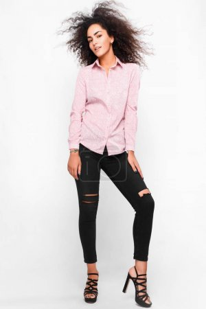 Photo for Fashionable portrait of beautiful young woman, wearing black skinny jeans, high heels, pink classic shirt, curly  fuzz hair, smiling, isolated on white background - Royalty Free Image