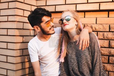 Stylish couple near the brick wall