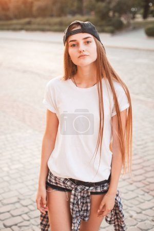 Photo for Young woman in white shirt and trucker hat standing on street - Royalty Free Image