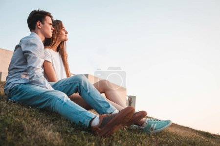 Young man and woman sitting on hill in city