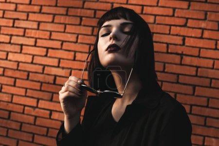 Photo pour Portrait de jeune femme avec des lunettes de soleil posant près d'un mur de briques - image libre de droit