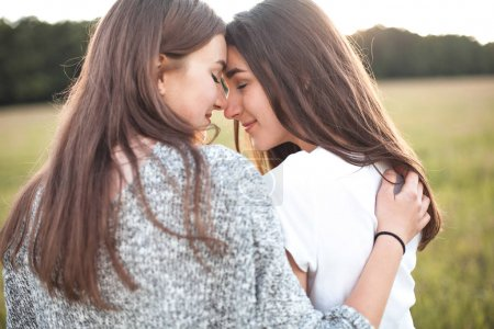Two girls hugging on green field in daytime