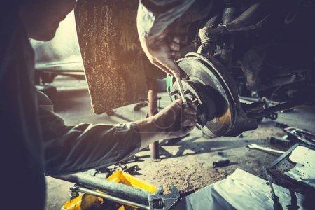 Photo pour Technicien travaillant sur le contrôle et l'entretien de la voiture dans le garage de l'atelier ; technicien réparation et entretien moteur de l'automobile en voiture servic - image libre de droit