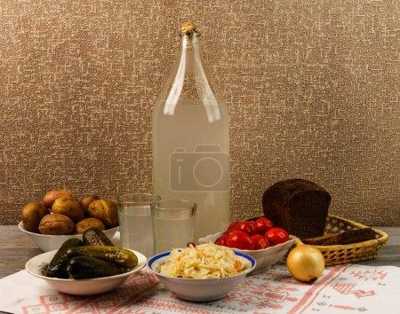 Photo pour Boisson nationale ukrainienne et collation. La bouteille et le verre d'alcool sur la vieille table en bois. Vodka russe et collation . - image libre de droit