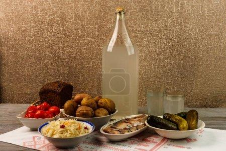 Photo pour Boisson nationale ukrainienne et collation. La grande bouteille et le verre d'alcool sur une vieille table en bois. Vodka russe et collation . - image libre de droit