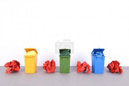 Colorful recycle bins on white background.