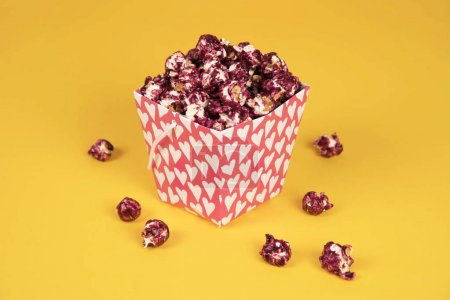 Pink popcorn with berry taste in paper cup on yellow background.