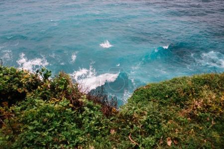 ocean waves under cliff with grass