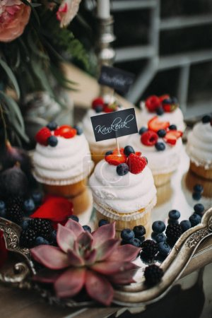 Photo for Delicious cupcakes on vintage tray with flowers decorations on table - Royalty Free Image
