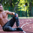 Young sporty man sitting at running track and rest...