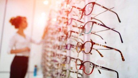 Rangée de lunettes chez un opticien. Boutique de lunettes. Stand avec des lunettes dans le magasin d'optique. La femme choisit les lunettes. Correction de la vue.