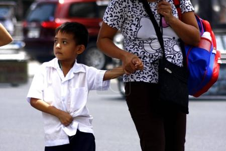 A young student walks with his mother going to school.