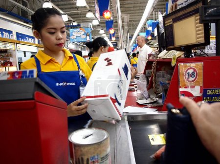 A cashier at a grocery store scans items a customer is buying.