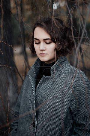 Photo pour Solitaire triste fille dans le sombre parc d'automne pluvieux - image libre de droit